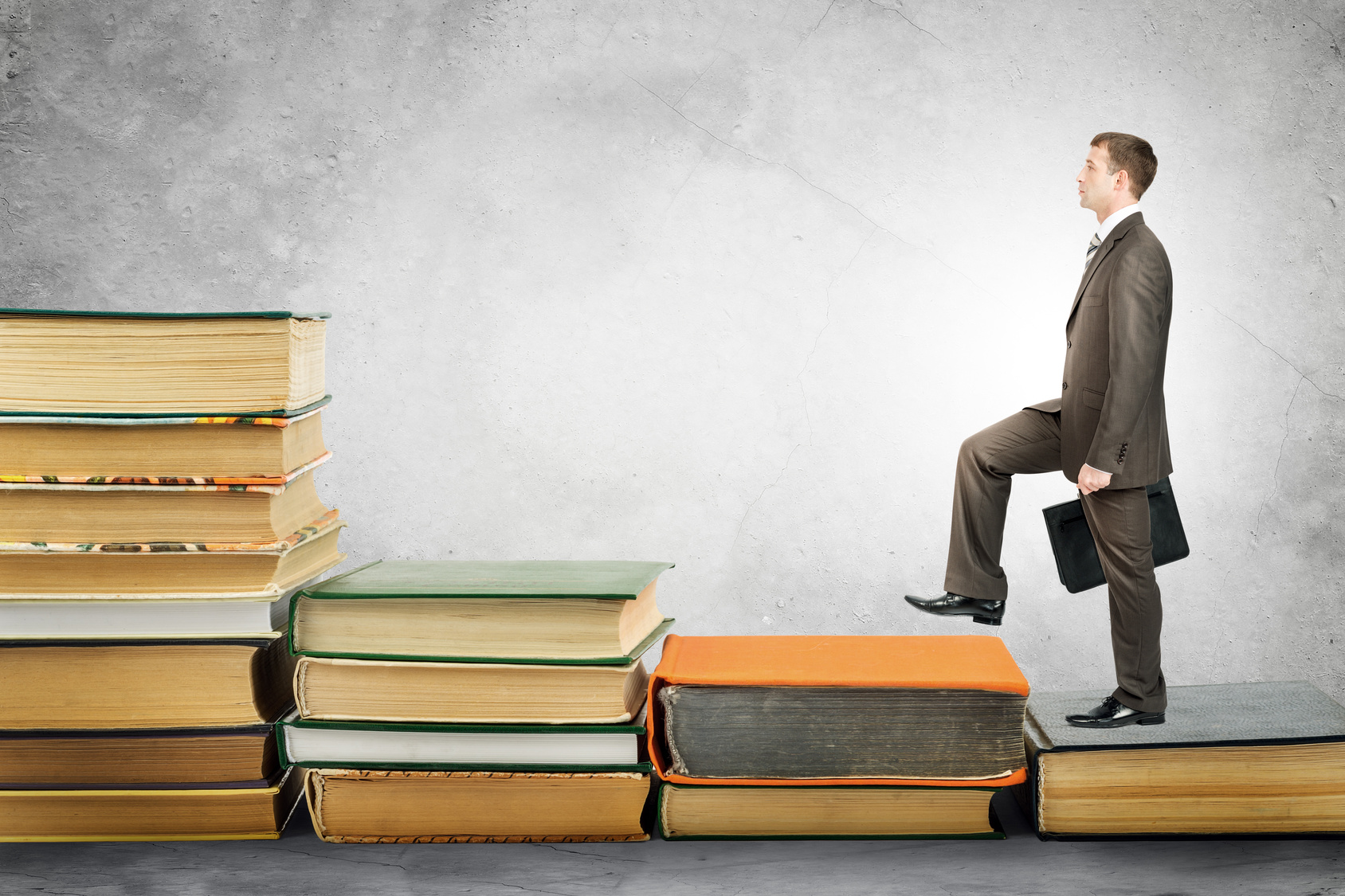 Businessman with portfolio goes up stairs of books